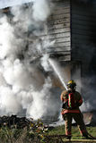 Firefighter Structure Fire. Firefighter working a hose on the corner of a burning structure Royalty Free Stock Photos