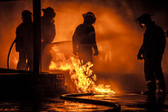 A Firefighter surrounded by flames Stock Image