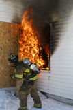 Firefighter tackling blaze Stock Photos
