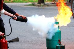 Firefighter teaching woman or man how to using fire extinguisher spraying form to fire royalty free stock photography