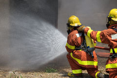 Firefighter team water spray by high pressure fire hose Royalty Free Stock Photography