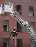 Firefighter during a training exercise with the autoscale and th. E rope to descend from above royalty free stock photo