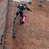 Firefighter during a training exercise climbing on old brick med Royalty Free Stock Photography