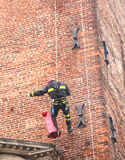 Firefighter during a training exercise climbing on old brick med Stock Photo