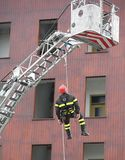Firefighter during a training exercise with the rope to descend. Firefighter during a training exercise with the autoscale and the rope to descend Stock Photos