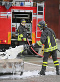Firefighter training and fire extinguishing with foam and truck Stock Photography