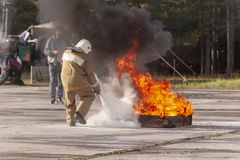 A fireman showing how to use a fire extinguisher on a training f royalty free stock image