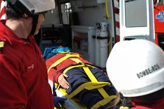 Firefighter transport patient on ambulance. Firefighters put litter patient on ambulance after road accident.This was a public demonstration on Matosinhos Royalty Free Stock Image