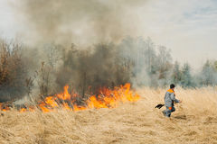 Firefighter try to suppress fire. BOYARKA, UKRAINE - 27 MART 2015: Firefighter or firemen on agriculture land fire. It was demonstration training of forest fire Royalty Free Stock Photo