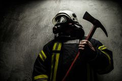 Firefighter in uniform. With axe on grey background Stock Photography
