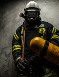 Firefighter in uniform. With axe and oxygen on grey background royalty free stock photo