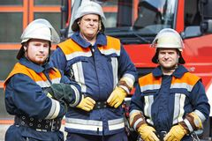 Firefighter. In uniform in front of fire engine machine and fireman team Stock Photos