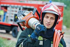Firefighter. In uniform in front of fire engine machine and fireman team Royalty Free Stock Image
