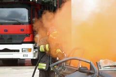 Firefighter uses a hydrant toward a car Royalty Free Stock Photos