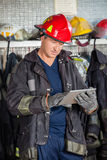 Firefighter Using Digital Tablet At Fire Station. Mature male firefighter in uniform using digital tablet at fire station Royalty Free Stock Photos