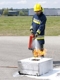 Firefighter using extinguisher Stock Photos