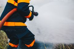 Firefighter using fire extinguisher and fire extinguisher. Firefighter using extinguisher and water from hose for fire fighting, Firefighter spraying high stock image