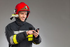 Firefighter using smart phone. Royalty Free Stock Image