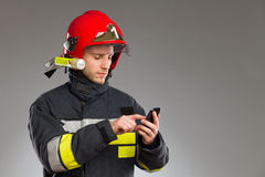 Firefighter using smart phone. Stock Photos