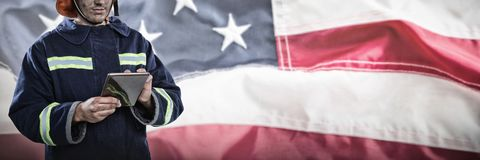 Composite image of firefighter using tablet. Firefighter using tablet against full frame of wrinkled american flag Royalty Free Stock Photos