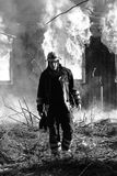 The Firefighter. Firefighter walking away from a burning house Royalty Free Stock Photography