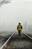 Firefighter Walking Rails. DAYTON, OHIO – AUGUST 15: Firefighter walks railroad track through haze of smoke and water mist during an old, abandoned warehouse Royalty Free Stock Photos