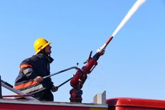 Fire fighting with water cannon. Firefighter with a water cannon extinguishes a fire Royalty Free Stock Photography