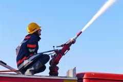 Firefighter on a water cannon. Firefighter with a water cannon extinguishes a fire Royalty Free Stock Photo