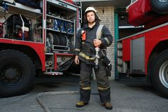 Firefighter with water hose near truck Stock Photos