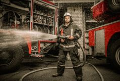 Firefighter with water hose near truck Stock Images