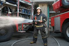 Firefighter with water hose near truck Royalty Free Stock Image