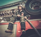 Firefighter with water hose near truck Royalty Free Stock Photography