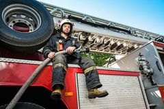 Firefighter with water hose near truck Stock Photography
