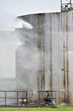 Firefighter water jet on big storage tank Royalty Free Stock Images