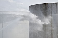 Firefighter water jet on big storage tank Stock Photo