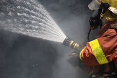 Firefighter water spray by high pressure fire hose surround with Royalty Free Stock Image