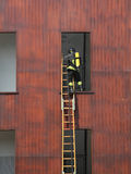 Firefighter on the wooden ladder enters the window Royalty Free Stock Image