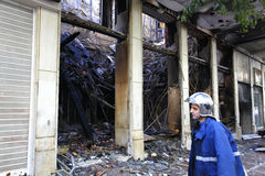 Firefighter at work. Firefighters at work looking at a burned store in Athens Stock Photos