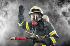 Firefighter at work. Firefighter giving directions in burning place Stock Photography