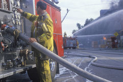 Firefighter working with fire hose Stock Photo