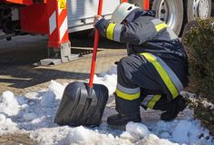 Firefighter works with a shovel in winter. Time Stock Images