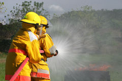 Firefighters. Two firefighter put out a fire using wide spray setting with the fire hose stock photography