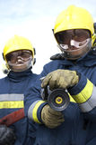 Firefighters. Firefighter holding fire hose to camera Stock Photo