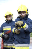 Firefighters. Portrait of firefighters holding hose to camera Royalty Free Stock Photos
