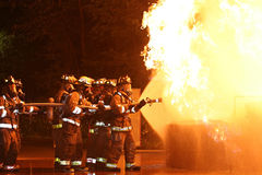 Firefighters. Fire fighters with fire hose spraying water into blazing fire Royalty Free Stock Photos