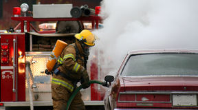 Firefighters. Firemen with burning car Royalty Free Stock Photography