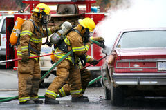 Firefighters. Firemen with burning car Royalty Free Stock Photos
