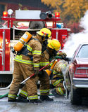 Firefighters. Firemen with burning car Stock Photo