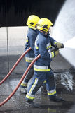 Firefighters in action. Two Firefighters working together using fire hose Stock Images