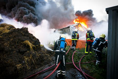 Firefighters in action. Firefighters in front of a huge fire Royalty Free Stock Images